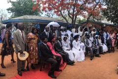 MASS WEDDINGS <p>Couples married in a mass wedding sponsored by a local non-governmental organisation (NGO) gather for a photo with the Minister for Local Government (centre, blue hat). Batswana link declining marriage rates with social and moral breakdown, and government, churches, and NGOs have taken an active role in brokering marriage.</p>